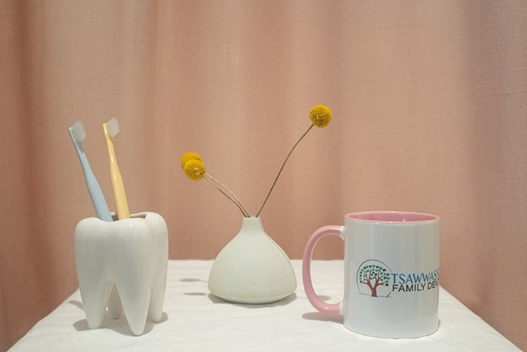 tooth sculpture with two toothbrushes, flower behind and Tsawwassen mug to the right