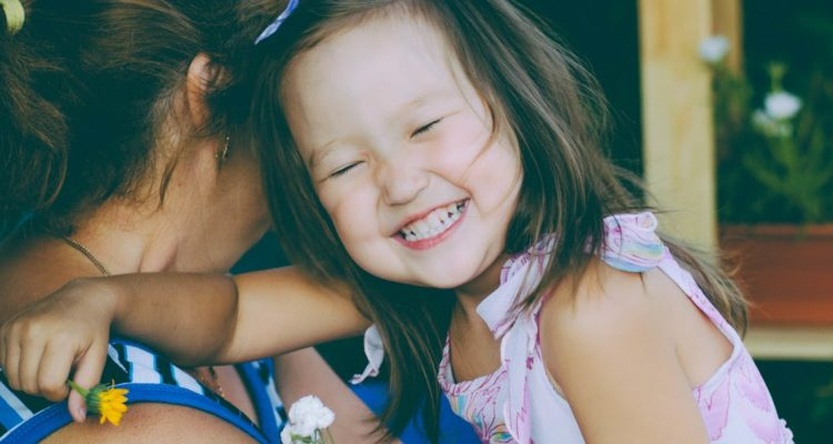 Toddler smiling in her mother's arms.