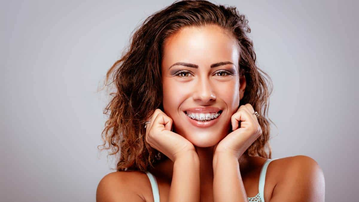 Woman with braces smiling and holding her hands to her chin.