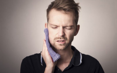 Man pressing a cloth to his jaw and looking pained.