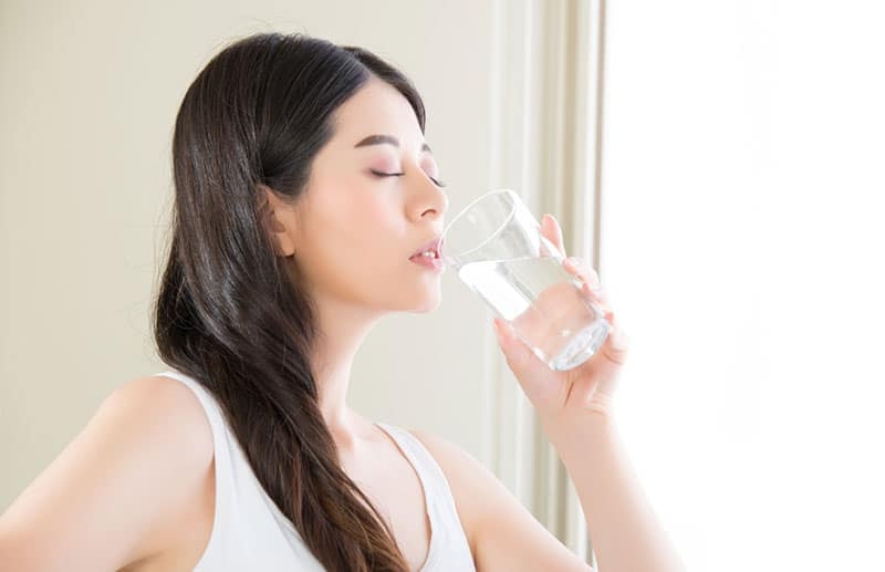 Woman in a white tank top drinking a glass of water.