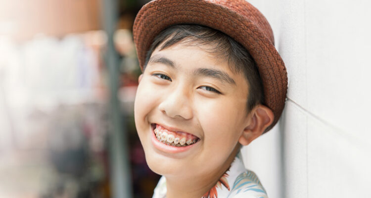 Smiling teenager with braces wearing a hat.