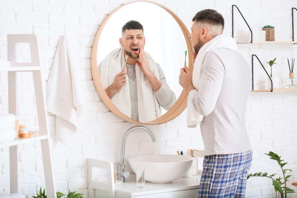 Man holding a toothbrush and looking at his mouth in a bathroom mirror.