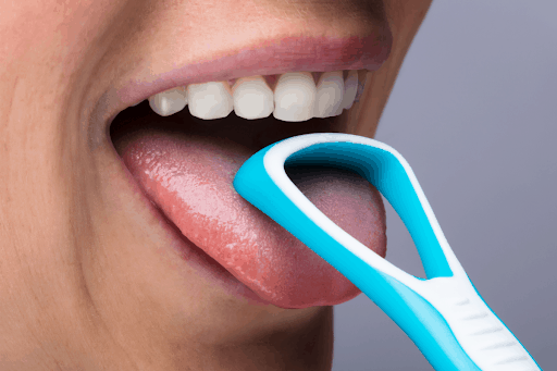 A person using a plastic scraper to clean their tongue.