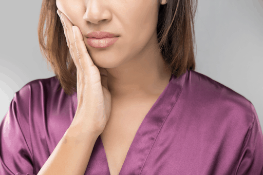 Woman in a purple shirt holding her jaw in pain.